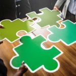 Four jigsaw puzzle pieces coming together