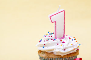 Cupcake with birthday candle of one year old isolated on plain background.